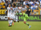 Seattle Sounders FC midfielder Gonzalo Pineda, right, kicks in front of Los Angeles Galaxy midfielder Juninho during the second half of a Major League Soccer playoff game, Sunday, Nov. 23, 2014, in Carson, Calif. The Galaxy won 1-0. (AP Photo/Mark J. Terrill)