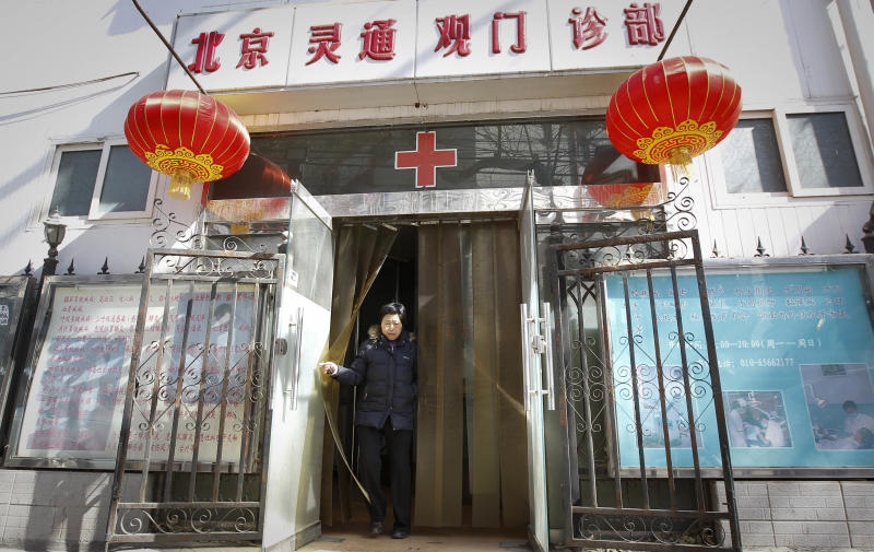 In this picture taken Tuesday March 8, 2011, a Chinese woman leaves a community clinic in downtown Beijing, China. Eight million more Chinese will be covered by the urban basic health insurance in 2011, the Ministry of Human Resources and Social Security said Wednesday. (AP Photo/Vincent Thian)