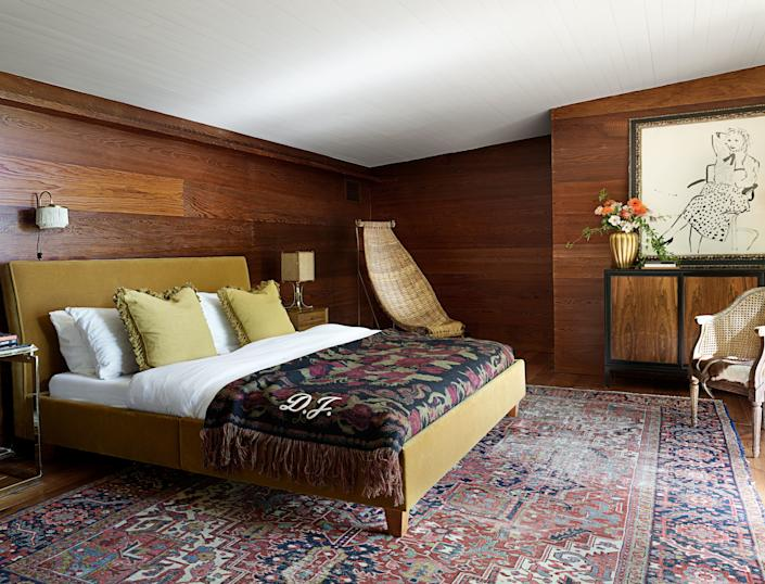 In the master bedroom, custom throw pillows and a Gucci blanket decorate the vintage bed. Vintage sconce and rattan chair; artwork by David Hockney.