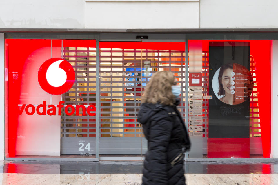 A woman wearing a face mask walks past a closed Vodafone store in Spain. Photo: Xisco Navarro/SOPA/Sipa USA