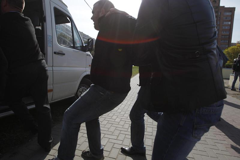 Belarus plainclothes security officers detain an opposition activist Paavel Vinogradov, during a protest in Minsk, Tuesday, Sept. 18, 2012. Associated Press photographer Sergei Grtts was beaten and briefly detained by plainclothes security officers in the Belarusian capital. Sergei Grits says he was among eight journalists covering a protest by four opposition activists calling for a boycott of this weekend's parliamentary elections when plainclothes security officers attacked them in downtown Minsk.(AP Photo/Sergei Grits)
