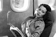 <p>Dutch actress Sylvia Kristel enjoys a cigarette and a book during a flight in 1974.</p>
