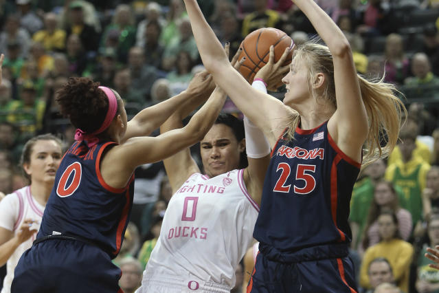 Arizona's Amari Carter, left, and Cate Reese, right, pressure Oregon's Satou Sabally during the second quarter of an NCAA college basketball game in Eugene, Ore., Friday, Feb. 7, 2020. (AP Photo/Chris Pietsch)