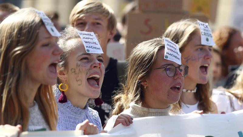 "Young women attend a 'Fridays For Future' rally in Munich, Germany, Friday, Sept. 20, 2019. The words on the sticker read: ""could have, would have, wanted, make"". Protests of the 'Fridays For Future' movement against the increase of carbon dioxide emissions are planned Friday in cities around the globe. In the United States more than 800 events were planned Friday, while in Germany more than 400 rallies are expected. (AP Photo/Matthias Schrader)"