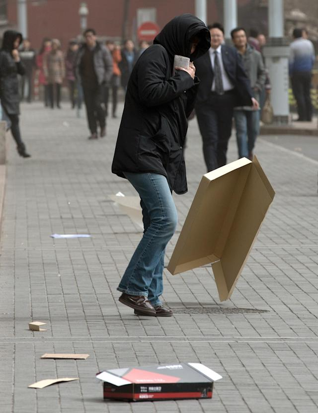 A woman covers her head while walking past a flying cardboard box after the capital city was hit by a sandstorm in Beijing Thursday, Feb. 28, 2013. (AP Photo/Andy Wong)