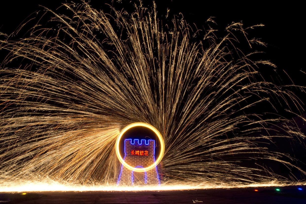 Performers turn a wheel spinning molten iron to create sparks at the Great Wall Iron Sparks show in Yanqing county on the outskirts of Beijing, China, Saturday, Jan. 28, 2017. An ancient craft that can be traced back several hundred years, the company is trying to revive the practice of throwing the molten iron and using the Lunar New Year period to showcase their latest choreography. Chinese character in center reads
