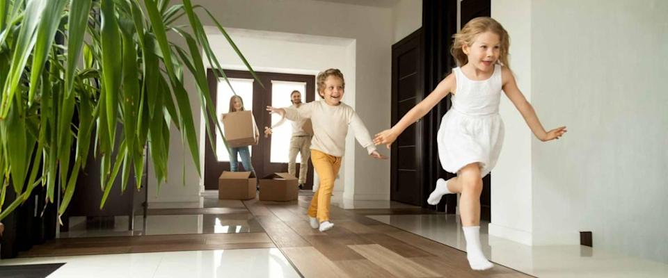 Happy young family with cardboard boxes in new home at moving day concept, excited children running into big modern home