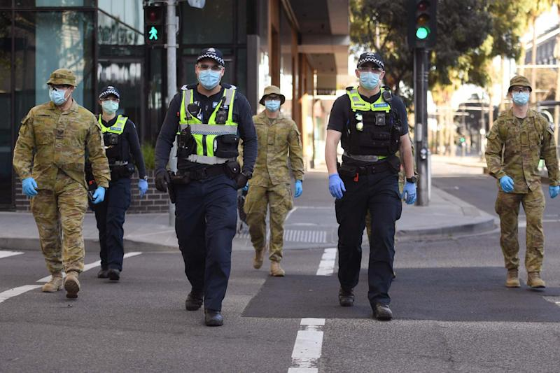 A group of police and soldiers patrol Melbourne after the announcement of new restrictions to curb the spread of Covid-19 (AFP via Getty Images)