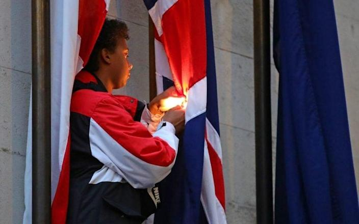 A protester attempts to burn a flag at the Cenotaph in Whitehall. - AARON CHOWN/PA
