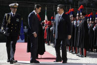 Chinese President Xi Jinping, right, and Italian Premier Giuseppe Conte walk past the honor guard during their meeting at Rome's Villa Madama, Saturday, March 23, 2019. (AP Photo/Andrew Medichini)