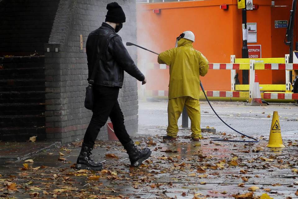 A man walks past a worker removing graffiti from a wall in London, Tuesday, Oct. 27, 2020. The British government is sticking to its strategy of tiered, regional restrictions to combat COVID-19 amid mounting political and scientific pressure for stronger nationwide measures to prevent the pandemic from spiralling out of control. (AP Photo/Kirsty Wigglesworth)