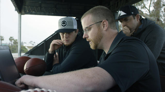 "In this April 19, 2018, photo provided by Wilson Sporting Goods, quarterback Sam Darnold, left, and his mentor, former quarterback Jordan Palmer, right, look on as Wilson Labs engineer Dan Hare explains data gathered from throwing a football using the Wilson Connected Football System, at San Clemente High School in San Clemente, Calif. Darnold, the New York Jets rookie quarterback, was at his old stomping grounds in California last month tossing ""smart"" footballs equipped with computer chips with Palmer, that were calculating his every throw. (Wilson Sporting Goods via AP)"