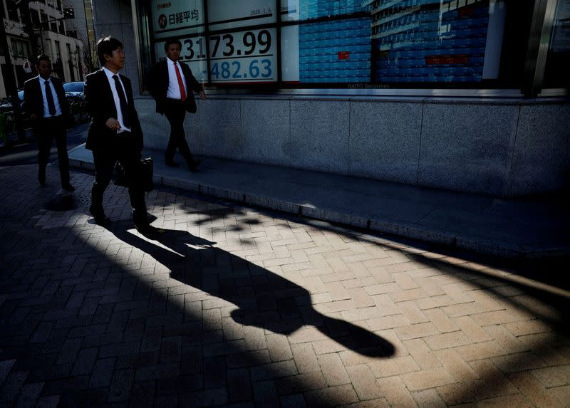 A man looks at a board showing stock prices outside a brokerage in Tokyo,