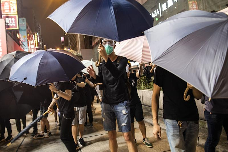 "(Bloomberg) -- Hong Kong police arrested five people while dispersing a protest Sunday in one of the financial hub's busiest tourist districts, the latest demonstration triggered by a proposed law that would allow extraditions of criminals to mainland China for the first time.Thousands of marchers walked through the pedestrian-heavy Tsim Sha Tsui area on a rainy Sunday toward the city's new high-speed rail station to China. By evening they had reached the main entrance, which had been closed off by authorities, and began surrounding the building.The crowd had largely dispersed by 9 p.m., but some people -- wearing the black shirts that have become the protest movement's unofficial uniform -- occupied Nathan Road in the commercial Mong Kok district, where they were confronted by lines of riot police.Five people were arrested for assaulting and obstructing a police officer when action was taken to disperse protesters, police said in statement early Monday. Police made repeated warnings to the protesters that they were taking part in unlawful assembly and urged them to leave, it said.This weekend's march follows weeks of demonstrations against the proposed extradition legislation. While Chief Executive Carrie Lam suspended the bill on June 15, protesters have continued pushing for its complete withdrawal, Lam's resignation and other demands.Ventus Lau, a protest organizer, said more than 230,000 people had joined the rally. Police -- whose turnout estimates are generally lower -- said 56,000 people had come out at the march's peak, according to Hong Kong broadcaster TVB.The size of the protest ""shows Hongkongers are very determined to fight until the very end,"" Lau said.The end point was intentionally chosen to reach out to mainland travelers using the rail link, according to postings and leaflets distributed by organizers. Some protesters waved flags that flew when Hong Kong was a British colony, while others carried yellow umbrellas, the symbol of the city's pro-democracy Occupy Central protests in 2014.It's not the first time Hong Kong protests have reflected anxiety that mainlanders are overwhelming the city -- and driving up the prices of goods for its residents. In 2015, demonstrators in Tuen Men and Tsim Sha Tsui scuffled with police as they rallied against traders who come to the city and purchase products to sell across the border.Why Hong Kong Is Protesting (and May Do So Again): QuickTakeProminent activist Joshua Wong joined the demonstrators and said they hoped to impress on mainland visitors the importance of freedom and human rights.""Even with the Great Firewall censorship, it's still a must for them to realize it's time to let Hong Kong people enjoy certain degree of autonomy, and that's the reason for us to continue our strike,"" he said.Lau said earlier in the day that barricades placed at the West Kowloon station could make it difficult for marchers to clear the streets at the end. ""If any danger appears, it will be the full responsibility of the police,"" Lau said.Last week, Hong Kong police began arresting suspects on charges related to the July 1 break-in of the Legislative Council, where protesters smashed glass windows and defaced walls, portraits of government officials and the Hong Kong emblem.Read more: Hong Kong Protester Who Defaced the City Emblem Is Still AngryA 53-year-old part-time art teacher who goes by the name Perry Dino was painting an image of the protest on his canvas outside West Kowloon station on Sunday as people marched.The government ""used a lot of money to build this station, but few people and only the mainland Chinese tourists use it,"" he said. ""Today may be the first day that a large amount of people came to this station. I wanted to come here and support the protesters.""\--With assistance from Justin Chin, Gregory Turk and Stephanie Chung.To contact the reporters on this story: Annie Lee in Hong Kong at olee42@bloomberg.net;Gregor Stuart Hunter in Hong Kong at ghunter21@bloomberg.netTo contact the editors responsible for this story: Brendan Scott at bscott66@bloomberg.net, Karen Leigh, Andrew DavisFor more articles like this, please visit us at bloomberg.com©2019 Bloomberg L.P."