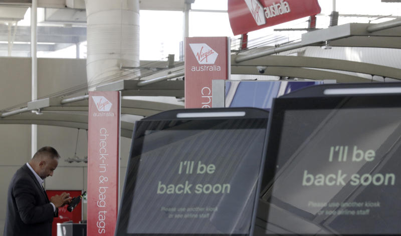 A Virgin Australia worker uses his phone at the check-in counters at Sydney Airport in Sydney, Wednesday, April 22, 2020. Virgin Australia is seeking bankruptcy protection, entering voluntary administration after a debt crisis worsened by the coronavirus shutdown pushed it into insolvency. (AP Photo/Rick Rycroft)