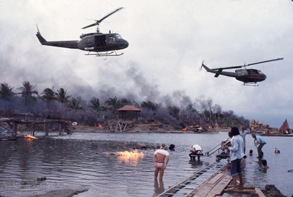 """<p>Director Francis Ford Coppola recreates a battle scene for Apocalypse Now in the Philippines. The film starring Robert Duvall, Martin Sheen, Dennis Hopper, Harrison Ford, Laurence Fishburne, and Marlon Brando was set to shoot for six months overseas, but instead took a <a href=""""https://www.imdb.com/title/tt0078788/trivia"""" rel=""""nofollow noopener"""" target=""""_blank"""" data-ylk=""""slk:grueling sixteen months"""" class=""""link rapid-noclick-resp"""">grueling sixteen months</a>. </p>"""