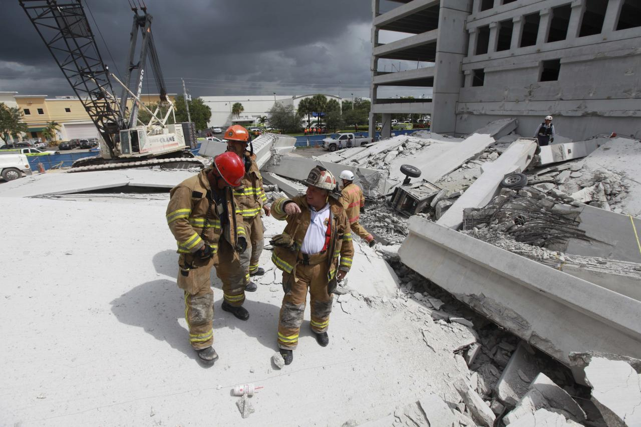 In a photo provided by Miami-Dade Fire Rescue, firefighters look over the rubble after a section of a parking garage under construction at a Miami-Dade College campus collapsed, Wednesday, Oct. 10, 2012 in Doral, Fla., killing one worker and trapping at least two others in the rubble, officials said. (AP Photo/Miami-Dade Fire Rescue)