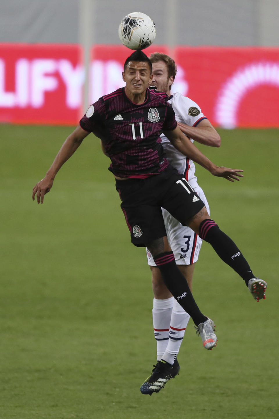Mexico's Roberto Alvarado (11) heads the ball challenged by United States' Henry Kessler during a Concacaf Men's Olympic Qualifying championship soccer match in Guadalajara, Mexico, Wednesday, March 24, 2021. (AP Photo/Fernando Llano)
