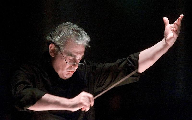 Mr Domingo conducts the orchestra during an opera rehearsal - AP Photo/Richard Drew