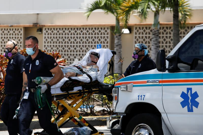 Emergency Medical Technicians (EMT) leave with a patient at Hialeah Hospital where the coronavirus disease (COVID-19) patients are treated