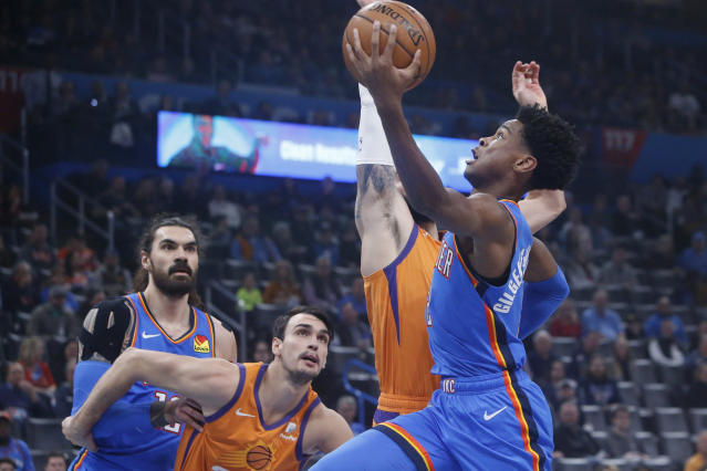 Oklahoma City Thunder guard Shai Gilgeous-Alexander, right, goes to the basket in front of teammate Steven Adams, left, and Phoenix Suns forward Dario Saric and guard Ricky Rubio during the first half of an NBA basketball game Friday, Dec. 20, 2019, in Oklahoma City. (AP Photo/Sue Ogrocki)