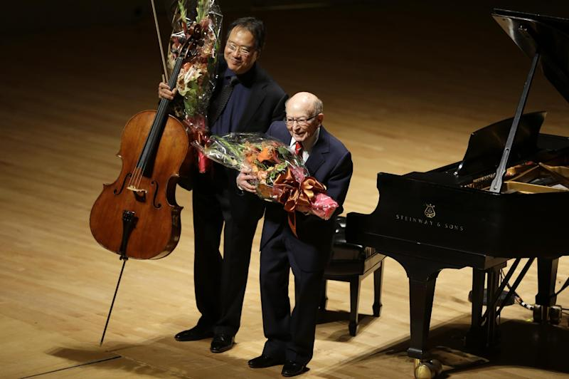 Cellist Yo-Yo Ma, left, and Holocaust survivor George Horner, right, hold flowers as they bow after performing together on stage at Symphony Hall Tuesday, Oct. 22, 2013, in Boston. The 90-year-old pianist made his orchestral debut with Ma, where they played music composed 70 years ago at the Nazi concentration camp where Horner was imprisoned. (AP Photo/Steven Senne)