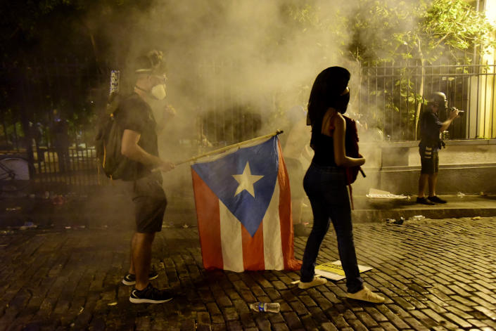 Demonstrators with a flag of Puerto Rico are under the tear gas thrown by the police during clashes near the executive mansion demanding the resignation of Gov. Ricardo Rossello, in San Juan, Puerto Rico, Wednesday, July 17, 2019. (Photo: Carlos Giusti/AP)