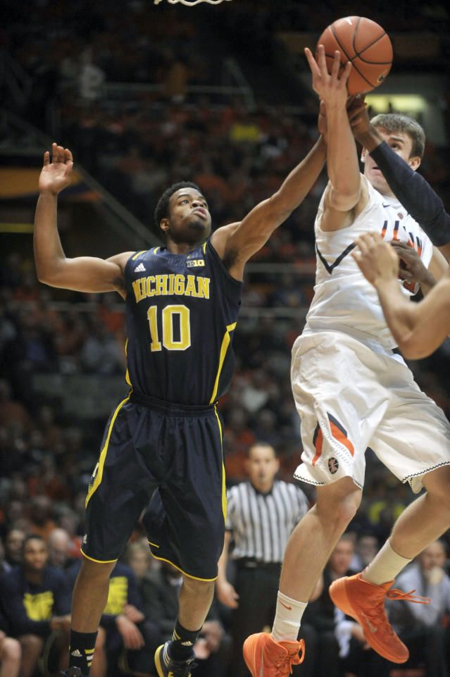 Michigan guard Derrick Walton Jr. (10) and Illinois forward Jon Ekey (33) vie for a rebound during the first half of an NCAA college basketball game Tuesday, March 4, 2014, in Champaign, Ill. (AP Photo/Rick Danzl)