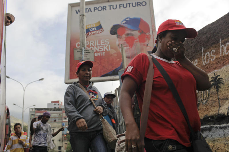 People walk by an old presidential election campaign poster supporting a vote for opposition candidate Henrique Capriles in Caracas, Venezuela, Monday, March 11, 2013.  Capriles, who lost a presidential election against Venezuela's late President Hugo Chavez in October 2012, announced he will run again on April 14th in an election to replace Chavez who died on March 5 after a nearly two-year bout with cancer. (AP Photo/Rodrigo Abd)