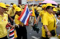 People carry flags and a portrait of King Maha Vajiralongkorn outside the balcony of Suddhaisavarya Prasad Hall at the Grand Palace, where he will grant a public audience to receive the good wishes of the people in Bangkok, Thailand May 6, 2019. REUTERS/Athit Perawongmetha