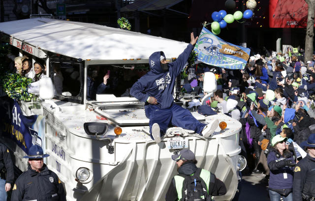 Seattle Seahawks' running back Marshawn Lynch throws pieces of candy while riding on the hood of a vehicle during the Super Bowl champions parade on Wednesday, Feb. 5, 2014, in Seattle. The Seahawks defeated the Denver Broncos 43-8 in NFL football's Super Bowl XLVIII on Sunday. (AP Photo/Ted S. Warren)