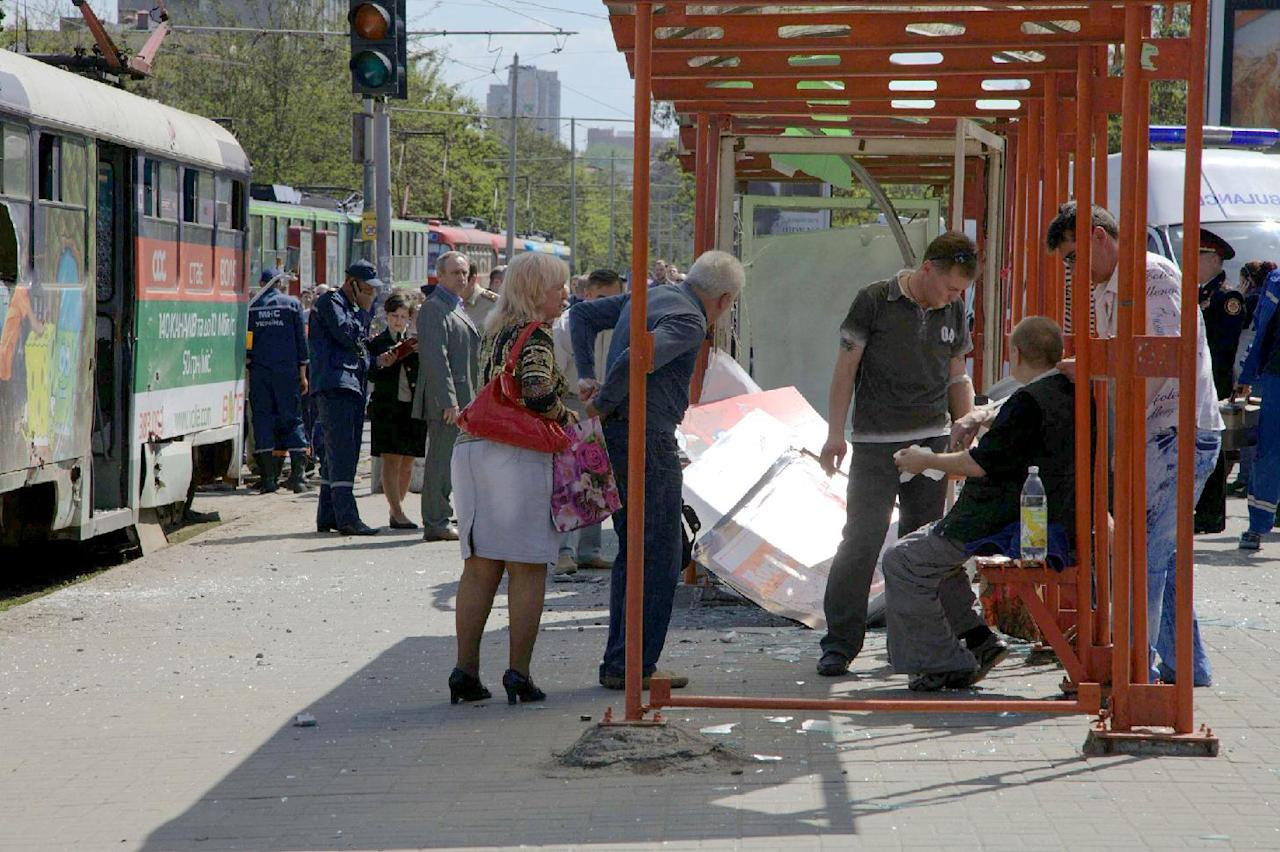 People assist injured after explosion in Dnipropetrovsk, Ukraine, Friday, April 27, 2012. Ukraine officials say dozens of people including schoolchildren were injured in four blasts in eastern city. (AP Photo/Dmitriy Dvorsky)