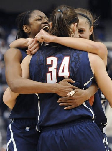 Connecticut's Tiffany Hayes, left, Kelly Faris (34) and Caroline Doty celebrate in the final minute of an NCAA college basketball game against Notre Dame in the final of the Big East women's tournament in Hartford, Conn., Tuesday, March 6, 2012. Connecticut won 63-54. (AP Photo/Jessica Hill)