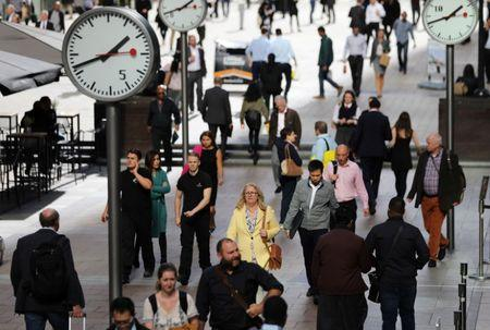 FILE PHOTO - People walk through the financial district of Canary Wharf, London, Britain 28 September 2017. REUTERS/Afolabi Sotunde -