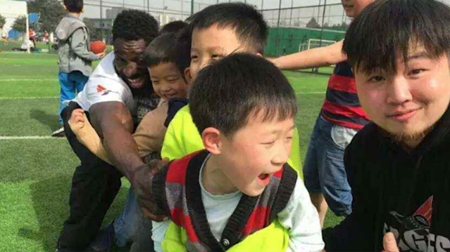 Wendell Brown teaches Chinese children how to play football during his tour in China. (AP)