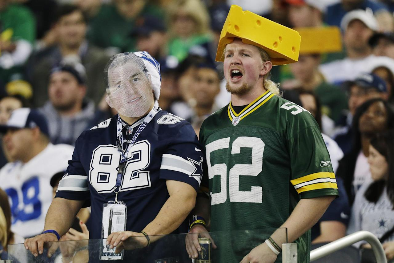 Dallas Cowboys and Green Bay Packers fans cheer during the first half of an NFL football game, Sunday, Dec. 15, 2013, in Arlington, Texas. (AP Photo/Tim Sharp)