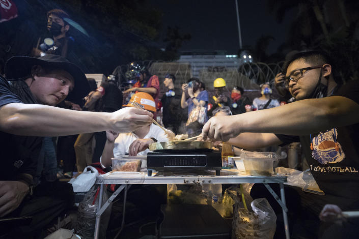 Pro-democracy protesters share a meal outside Police headquarters during a rally in Bangkok, Thailand, Wednesday, Nov. 18, 2020. Police in Thailand's capital braced for possible trouble Wednesday, a day after a protest outside Parliament by pro-democracy demonstrators was marred by violence that left dozens of people injured. (AP Photo/Wason Wanichakorn)