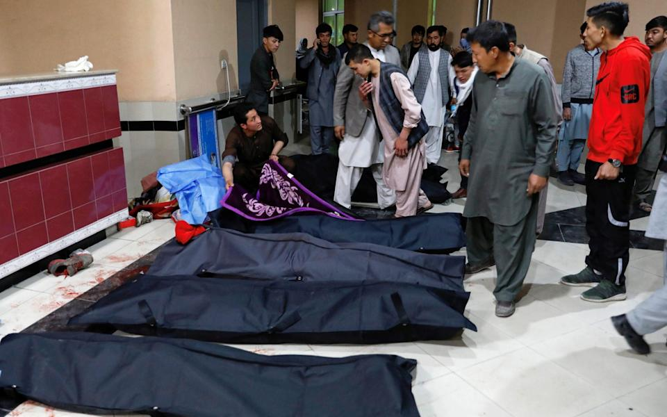 Afghan men look for their relatives at a hospital after the bombing - REUTERS