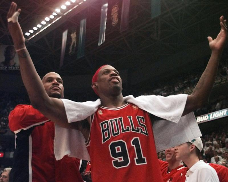 The Chicago Bulls' Dennis Rodman gestures to the crowd in front of Ron Harper at the end of Game 5 of the NBA Finals with the Utah Jazz on Wednesday, June 11, 1997, in Salt Lake City. The Bulls beat the Jazz 90-88 to take a 3-2 lead in the series as the teams head back to Chicago for Game 6 on Friday. (AP Photo/Jack Smith)