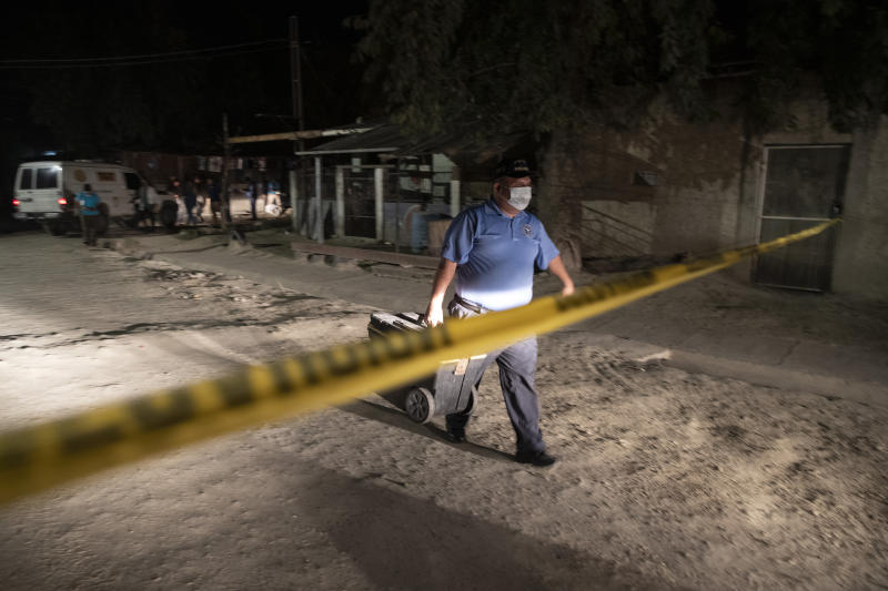 A forensic worker leaves a crime scene after inspecting the body of a man fatally shot in the streets of the Rivera Hernandez neighborhood in San Pedro Sula, Honduras, on Nov. 30, 2019. There are police stations in these neighborhoods, but everyone knows who is in charge. The gangs monitor the streets, the police patrols and rival gangs using a complex network of young boys who work in shifts around the clock and report anything suspicious. (AP Photo/Moises Castillo)