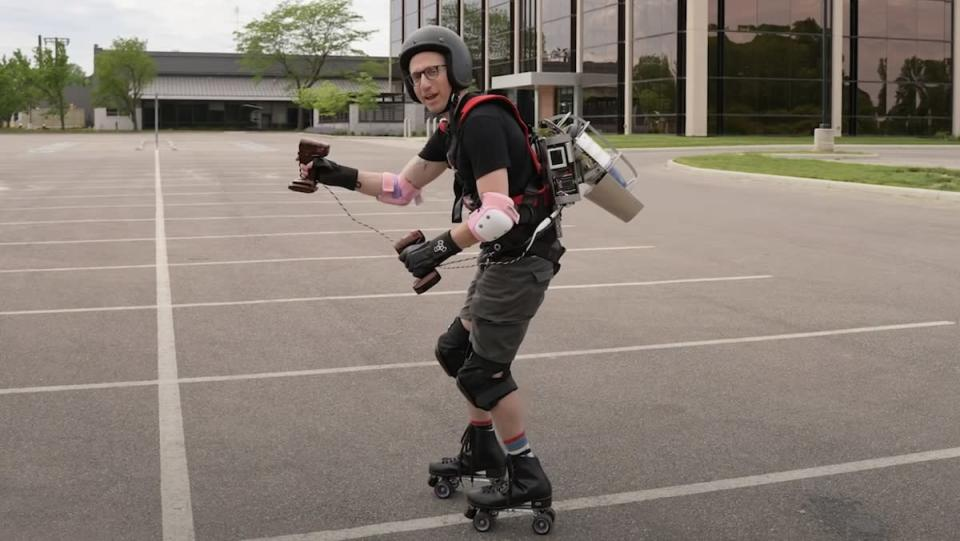 A man wears a jetpack, helmet, and roller skates outside in a parking lot