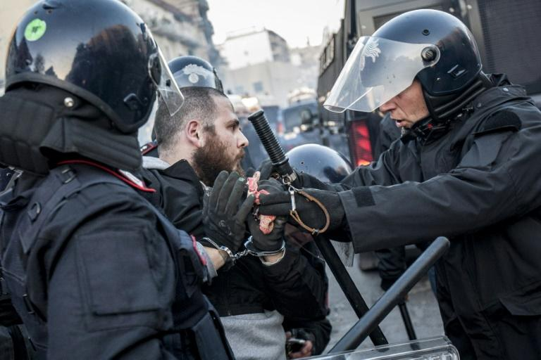 Anti-riot policemen arrest a man during clashes with a group of rioters during a rally against the political meeting of Matteo Salvini, general secretary of far-right party Lega Nord in Naples on March 11, 2017