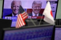 A monitor showing the reports on the U.S. presidential election are seen between the U.S. and Japanese national flags at a foreign exchange trading company's dealing room in Tokyo
