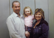 In this 2006 photo provided by the family, Paul and Judy Neiman hold their daughter, Sydnee, who died in late 2011 after Judy accidentally backed over her with her SUV. Although there is a law in place that calls for new manufacturing requirements to improve the visibility behind passenger vehicles, the standards have yet to be mandated because of delays by the U.S. Department of Transportation. (AP Photo/Courtesy of Judy Neiman)