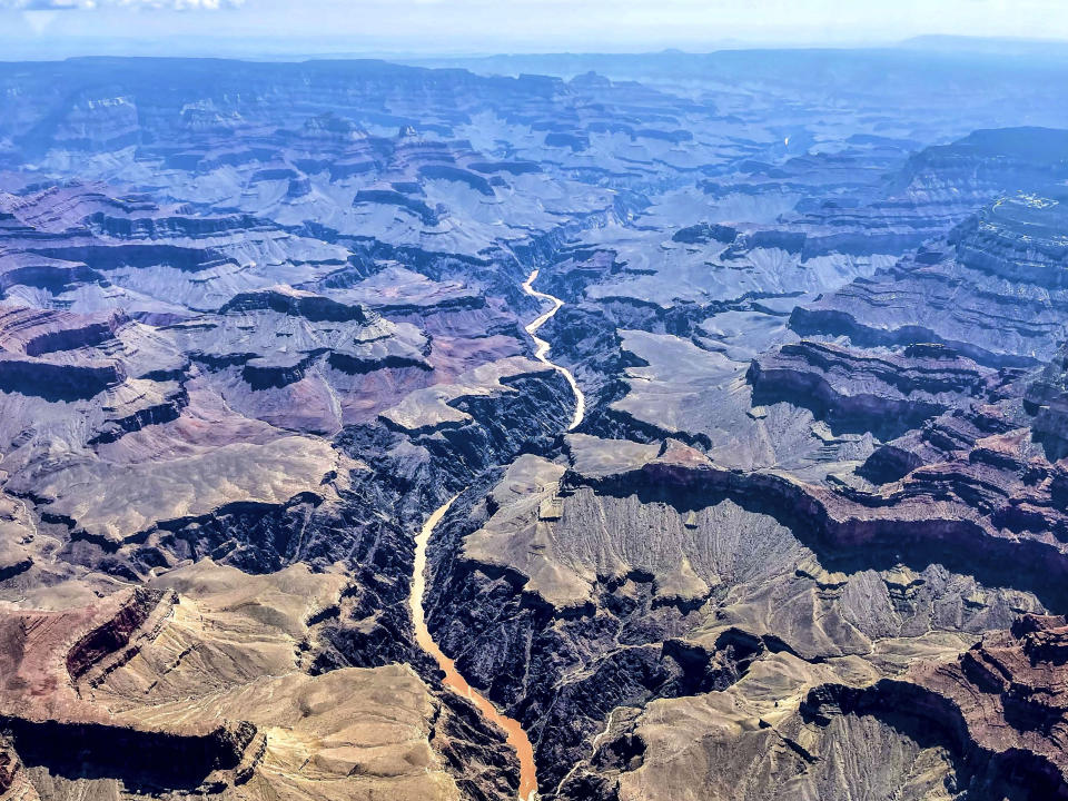 This photo provided by John Dillon shows the effects of flooding in the Colorado River through the Grand Canyon on Thursday, July 15, 2021. The river that's normally a greenish color turned a muddy brown from flash floods that have inundated Arizona. Authorities are searching for two people who were on a river rafting trip through the Grand Canyon and went missing after a flash flood, a park spokeswoman said Thursday. (John Dillon via AP)