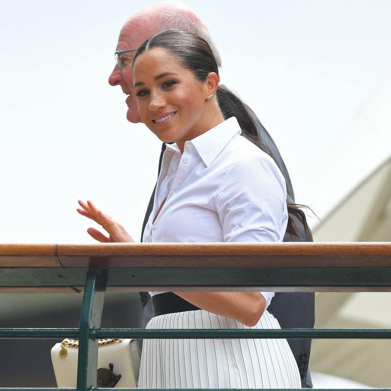 <p>Then Meghan arrived, just ahead of the start of the match. She chose to wear a crisp white blouse paired with a bold Hugo Boss skirt for today's appearance.</p>