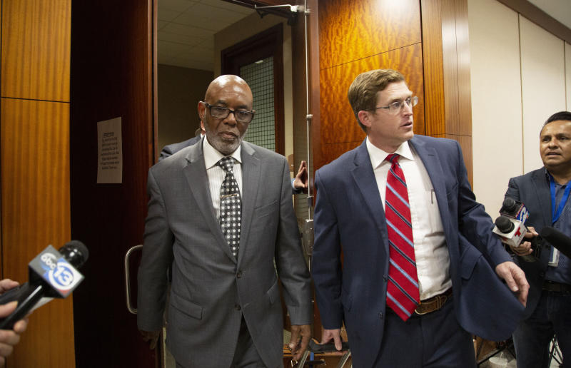 FILE - In this Jan. 9, 2020, file photo, Otis Mallet, center, exits the 338th District Criminal Court with his lawyer Jonathan Landers, right, in Houston. Prosecutors said Wednesday, Feb. 12, they believe Otis Mallet's brother, Steven Mallet, who was convicted based on what they allege is false testimony by an ex-Houston police officer whose cases are being reviewed following a 2019 deadly drug raid, is actually innocent. Earlier this month, Otis Mallet was declared innocent by a judge after his attorneys and prosecutors agreed that the ex-Houston police officer had lied during his trial about buying drugs from the brothers and had failed to provide evidence that would have helped their case. (Marie D. De Jesus/Houston Chronicle via AP, File)