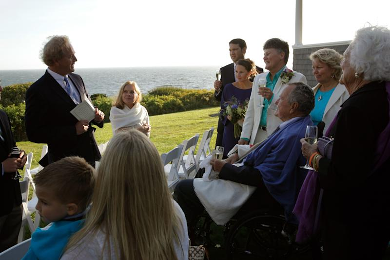 In this Sept. 21, 2013 photo, Erling Thorgalsen, at left, makes a toast in honor of his sister, Helen, second right, and Bonnie Clement, fourth right, after their wedding, as longtime friends former President George H.W. Bush, seated third right, and former first lady Barbara Bush, right, listen, in Kennebunkport, Maine. Bush was an official witness at the same-sex wedding, his spokesman said Wednesday, Sept. 25, 2013. (AP Photo/Susan Biddle)