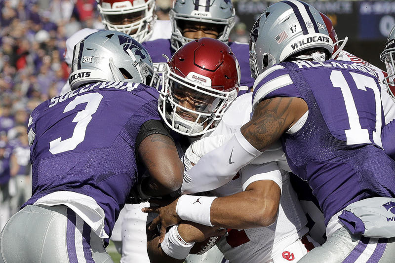Oklahoma quarterback Jalen Hurts, center pushes his way into the end zone to score a touchdown during the first half of an NCAA college football game against Kansas State Saturday, Oct. 26, 2019, in Manhattan, Kan. (AP Photo/Charlie Riedel)