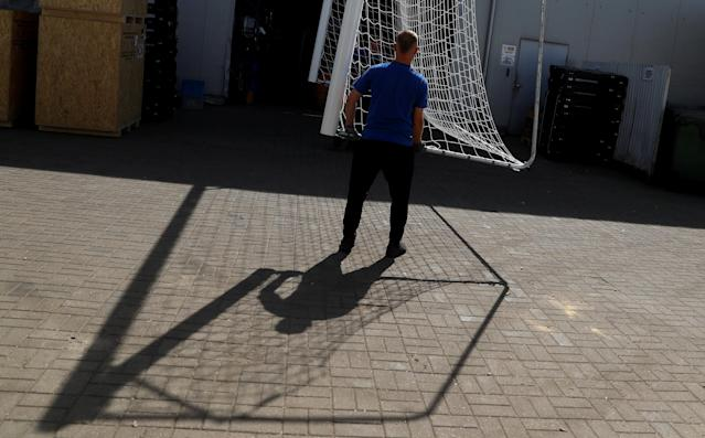 Workers hold a goal at Interplastic, a Polish manufacturing company who are supplying the football goalposts for the 2018 World Cup finals in Russia, in Chwaszczyno, Poland, May 16, 2018. Picture taken May 16, 2018. REUTERS/Kacper Pempel